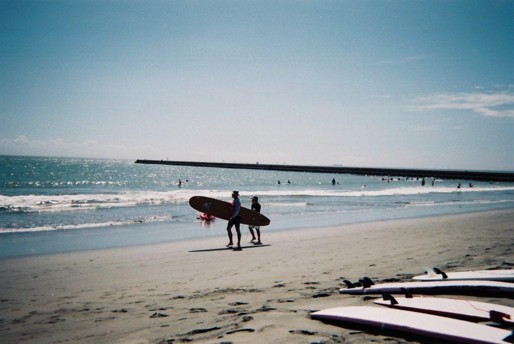 サーフボードを抱える人