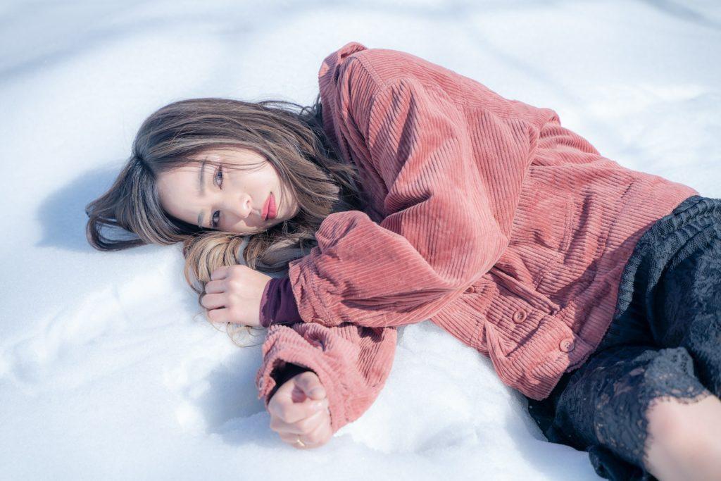 雪の上で転がる女性